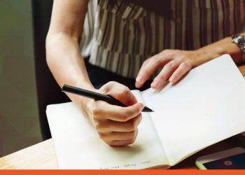 Auditora a escrever dados num caderno durante processo de auditoria